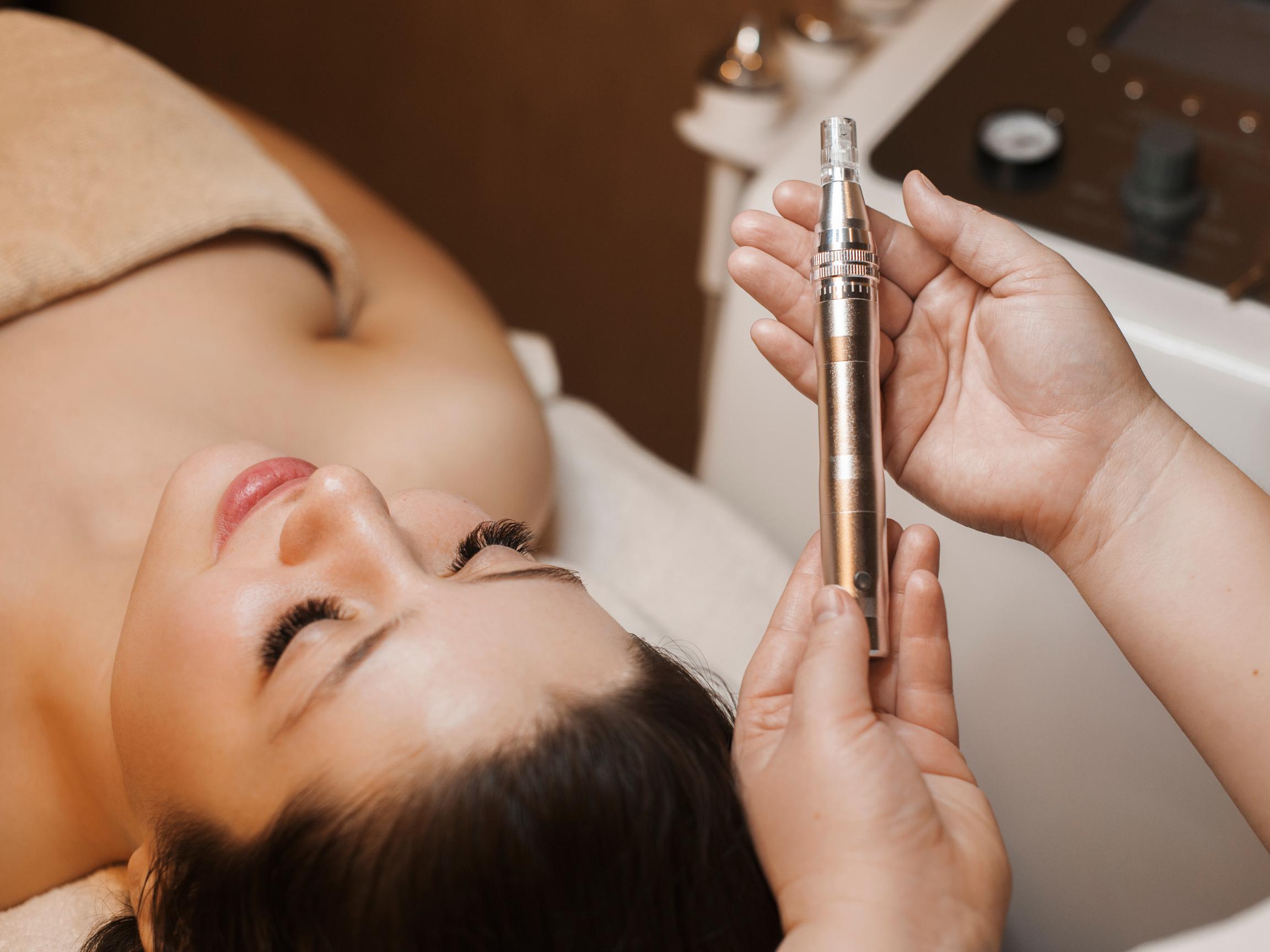 woman lying down preparing for microneedling treatment
