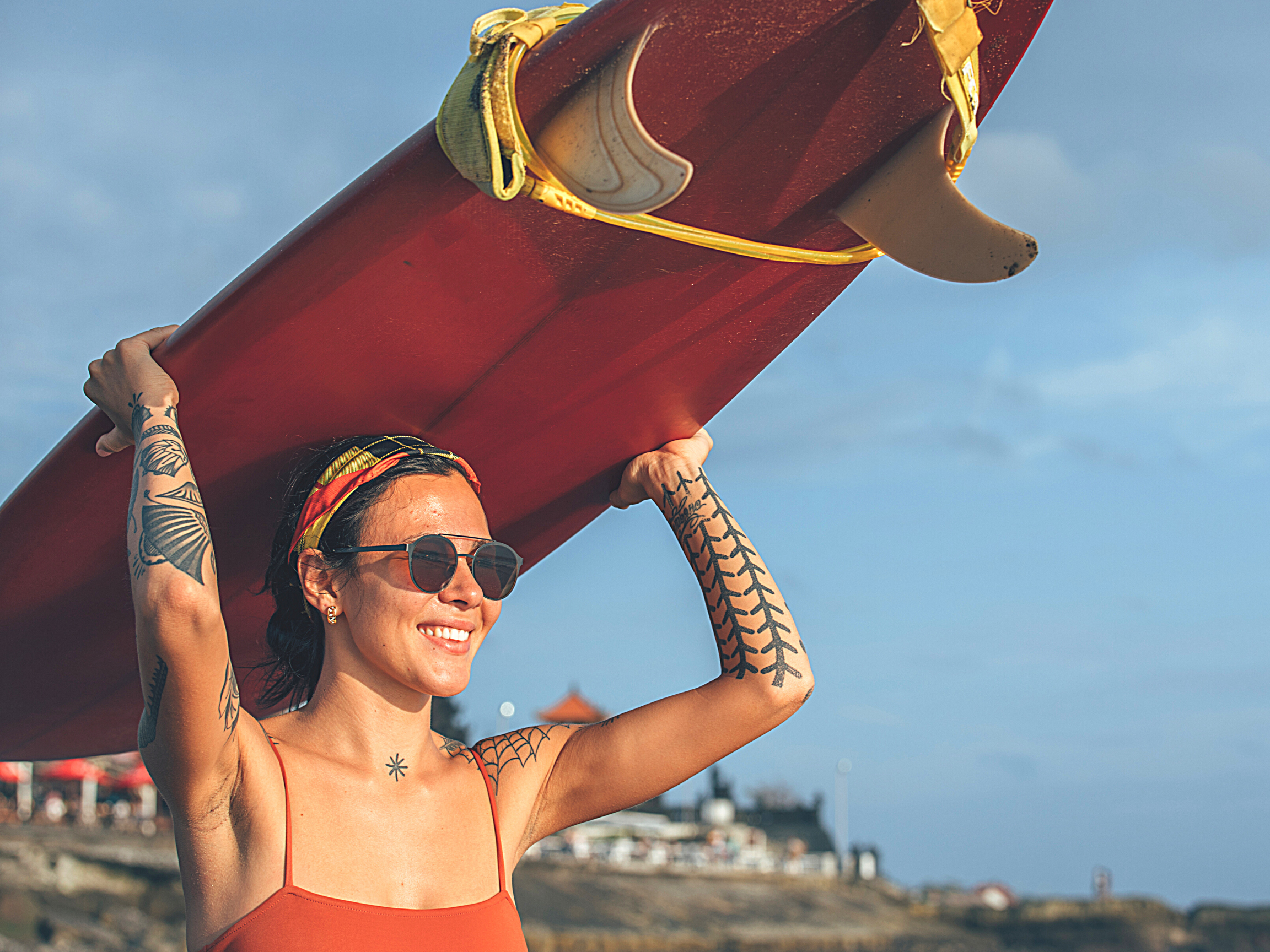 smiling tattooed woman wearing sunglasses and carrying a surfboard