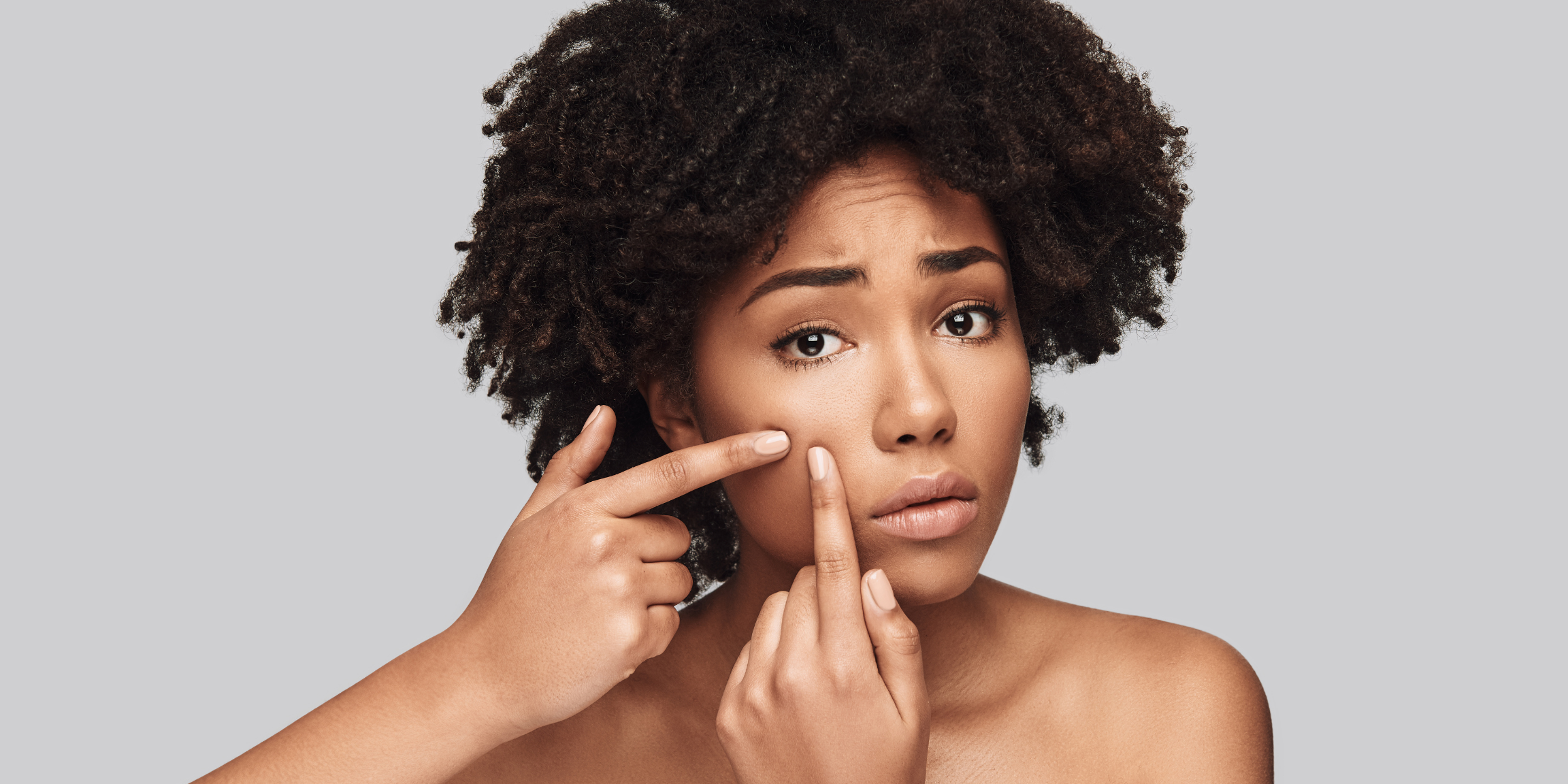 woman looking concerned and touching her skin, about to squeeze a pimple