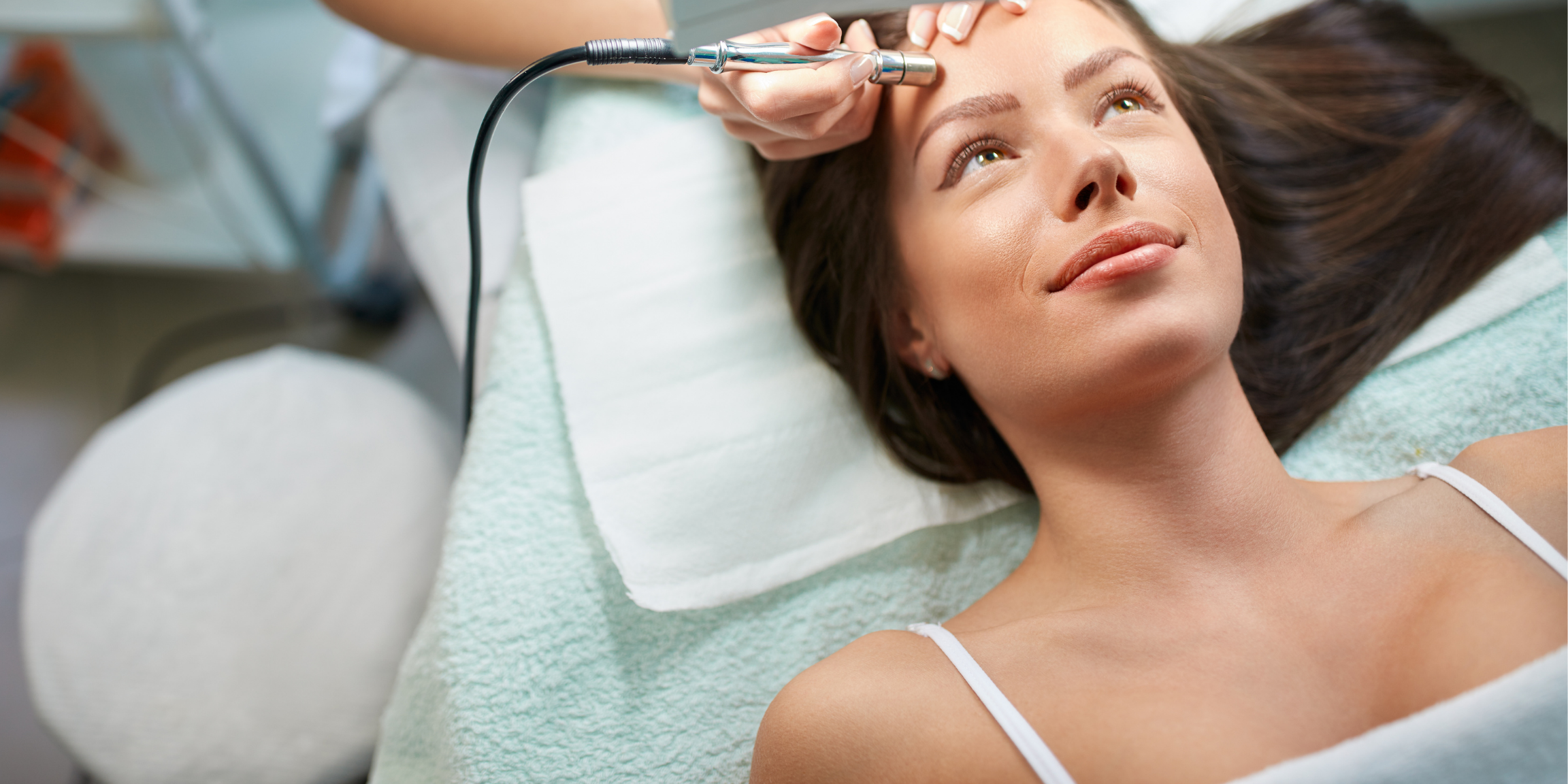 woman smiling, lying down, and receiving a microdermabrasion treatment