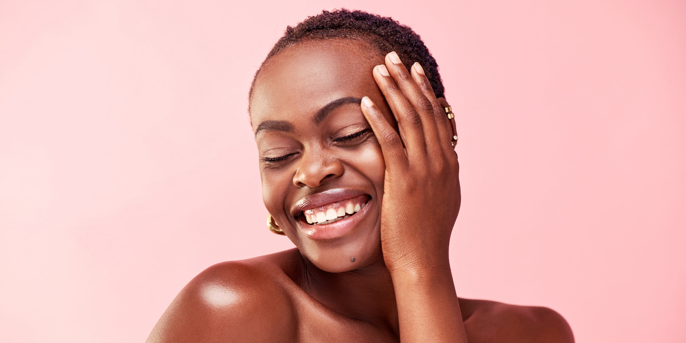 beautiful woman touching her skin and smiling with her eyes closed
