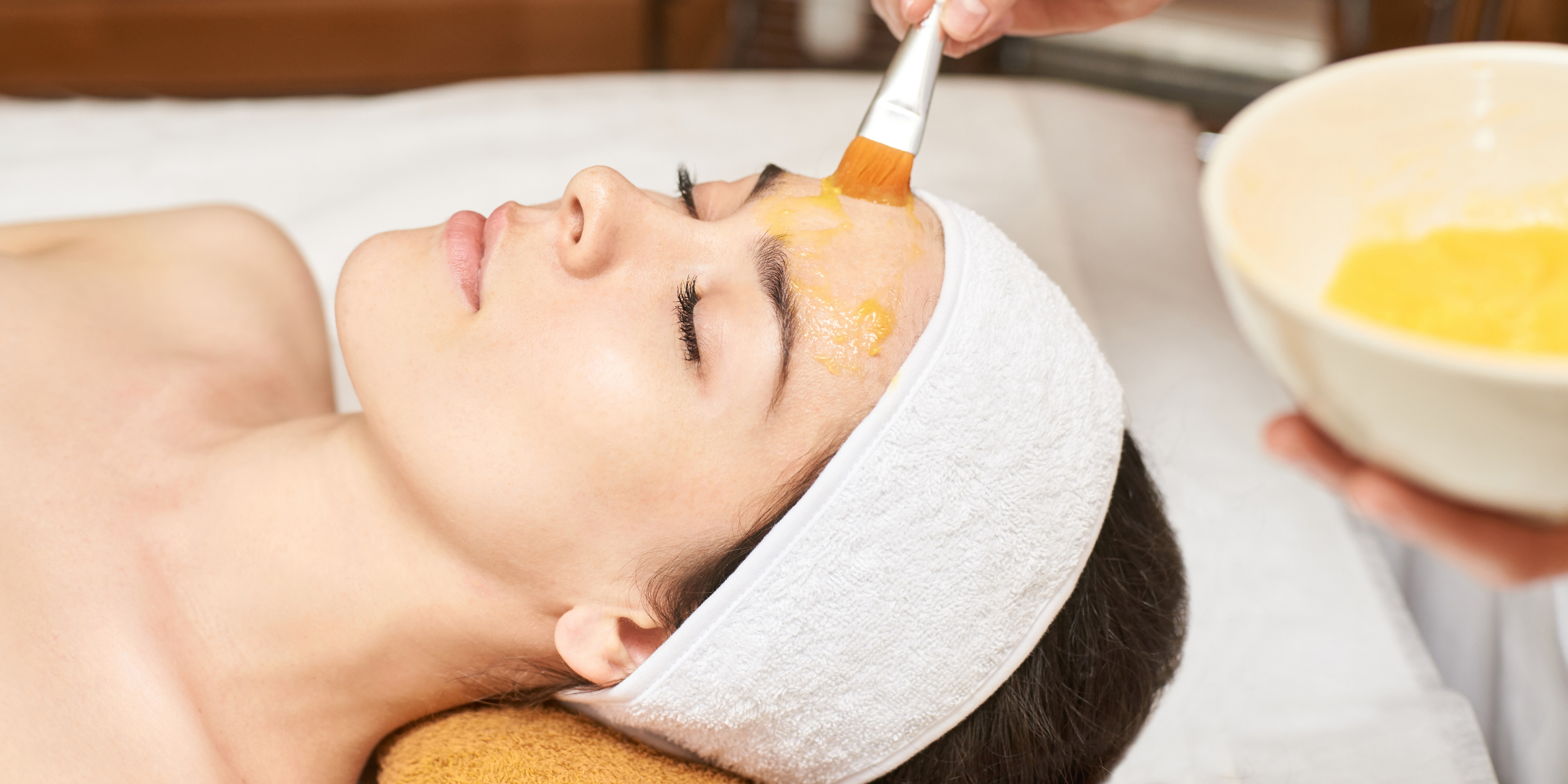 woman with skincare products being painted onto her face during a professional facial